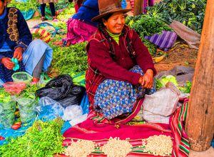 Frau verkauft Gemüse in einem Marktstand im heiligen Tal der Inkas, Peru